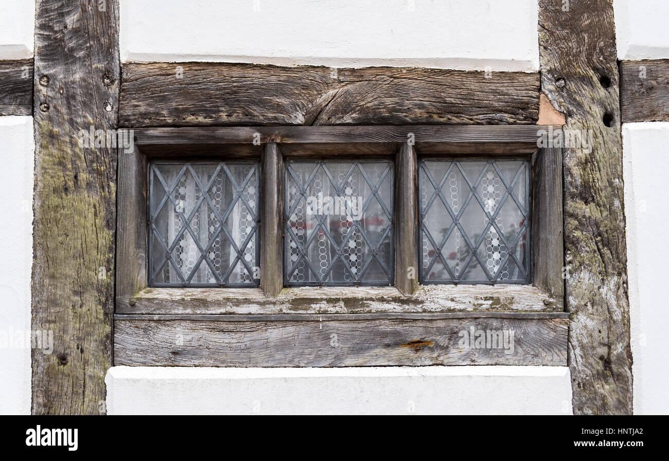 Tudor period window frame, in plain white wall - Stock Image