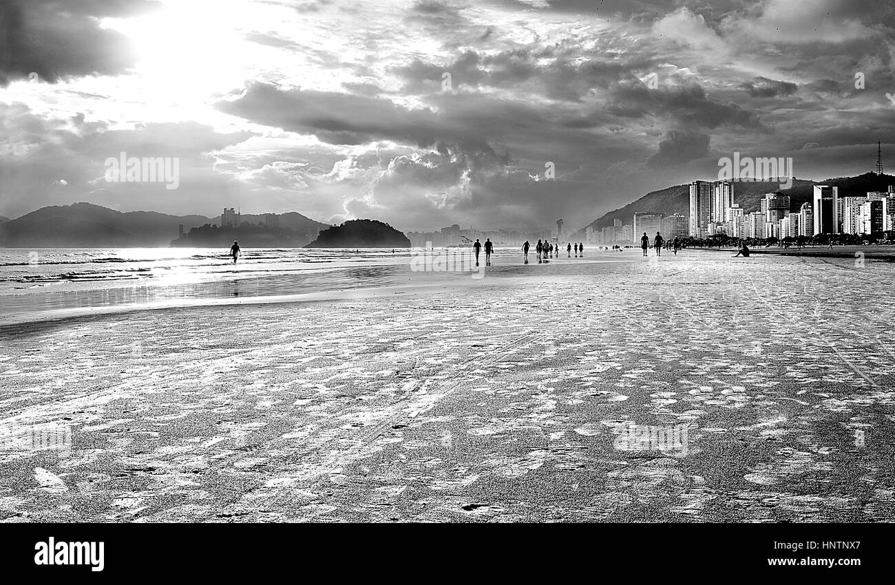 Silver Beach. A beach during sunset with people walking in the sand - black and white artistic version - Stock Image