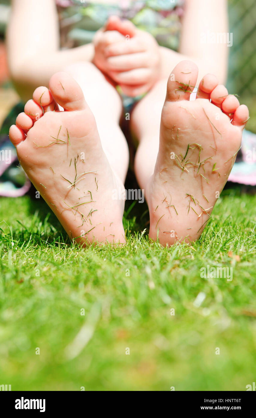 four year old girl in a garden with grass cuttings on the soles of