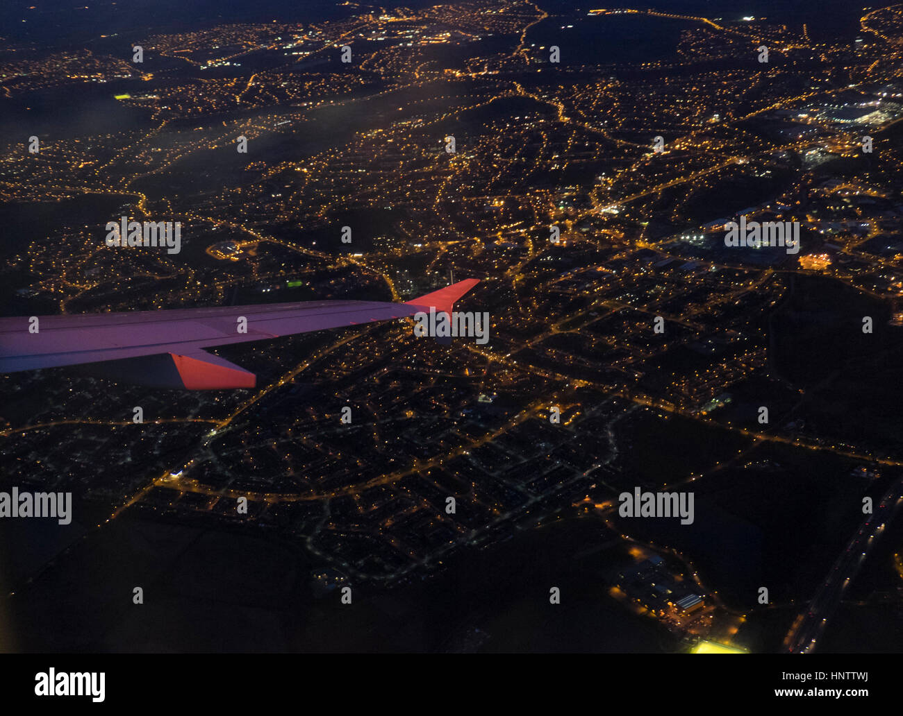 A city at night as seen from an aeroplane window - Stock Image