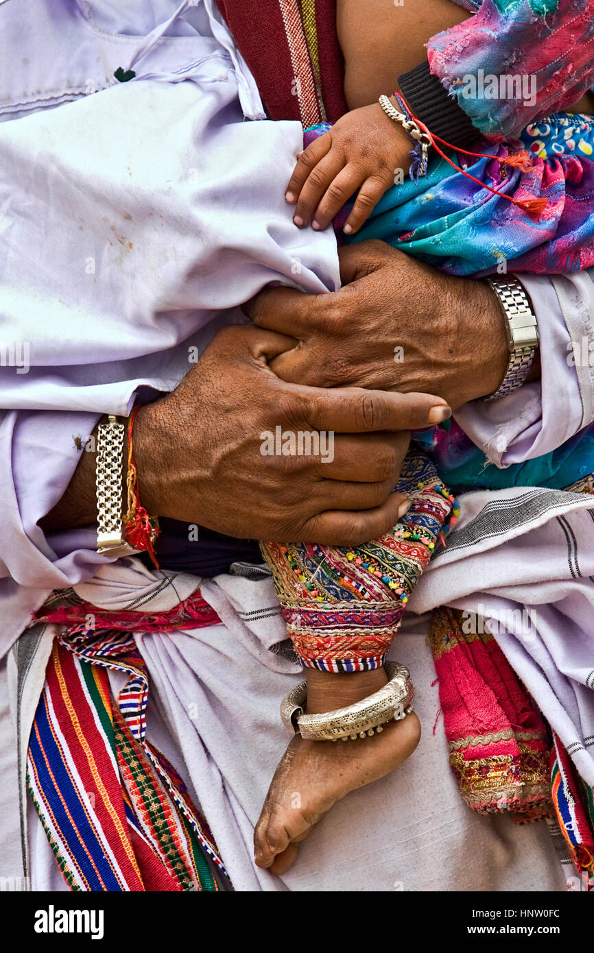 Hands and legs of father and son, from interior village of Kachchh, India, wearing traditional clothes and ornaments - Stock Image