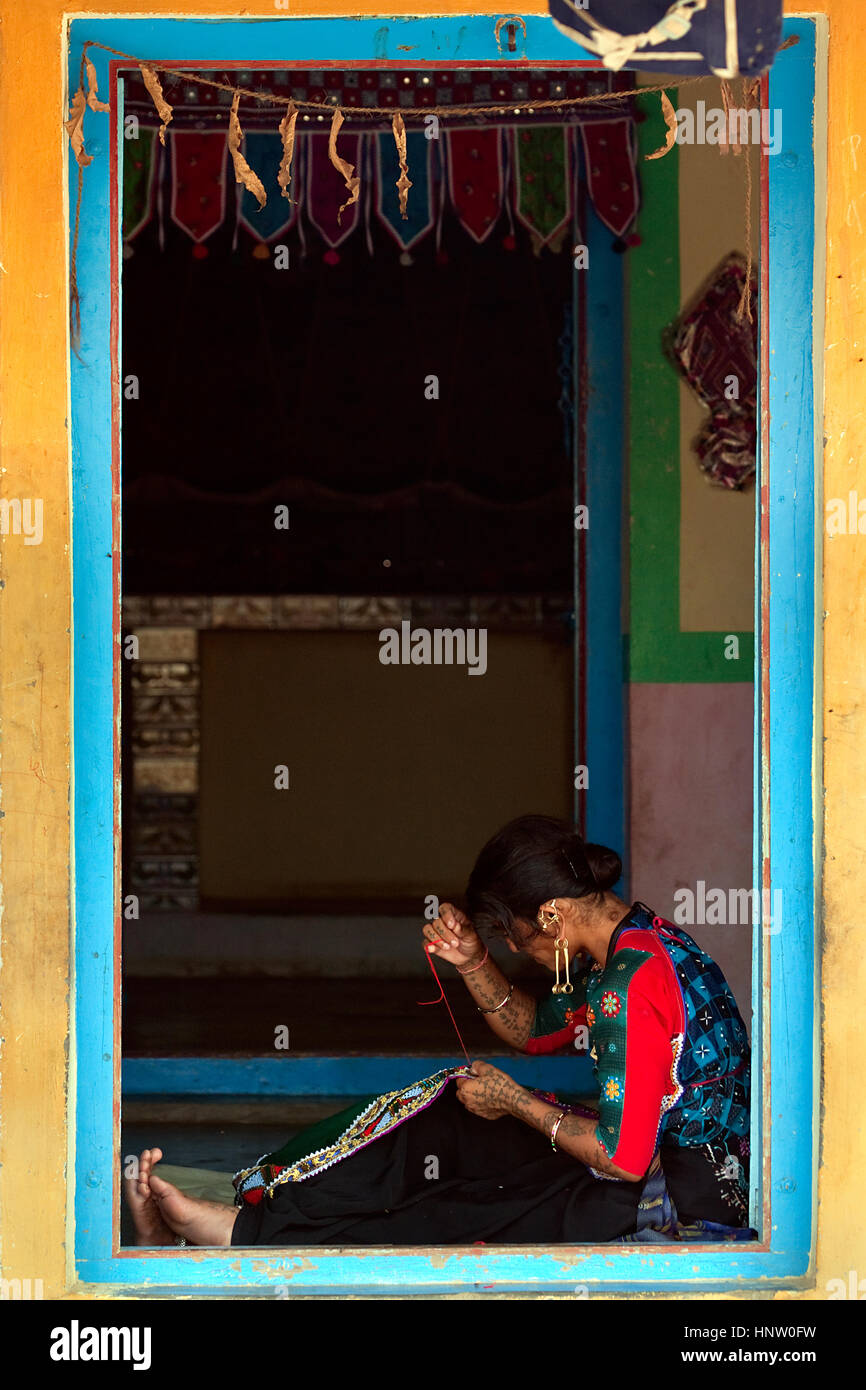 A Kutch/Kachchh woman sitting on the floor at the open door of the house, stiching, doing handicraft - Stock Image