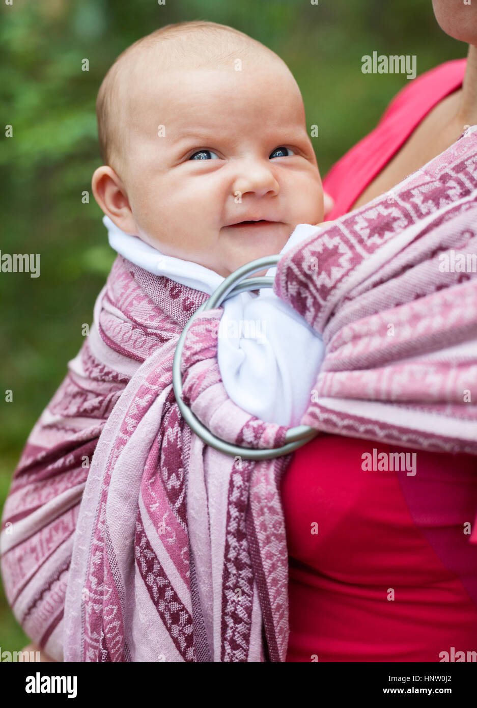 Mother carrying her child in a baby sling - Stock Image