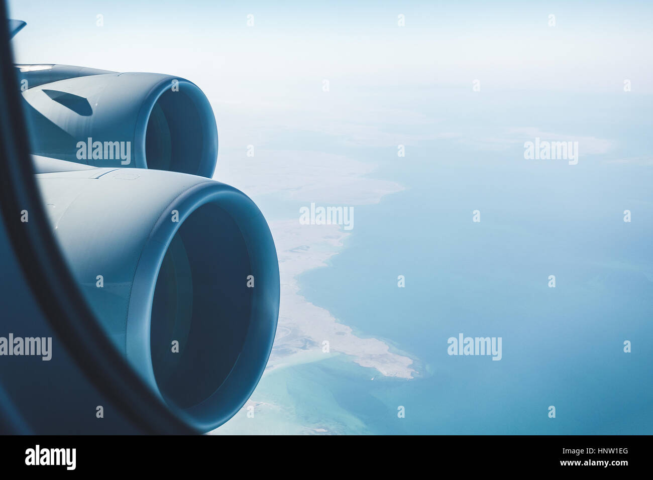 Airliner jet engines and coastal landscape, airplane in flight - Stock Image