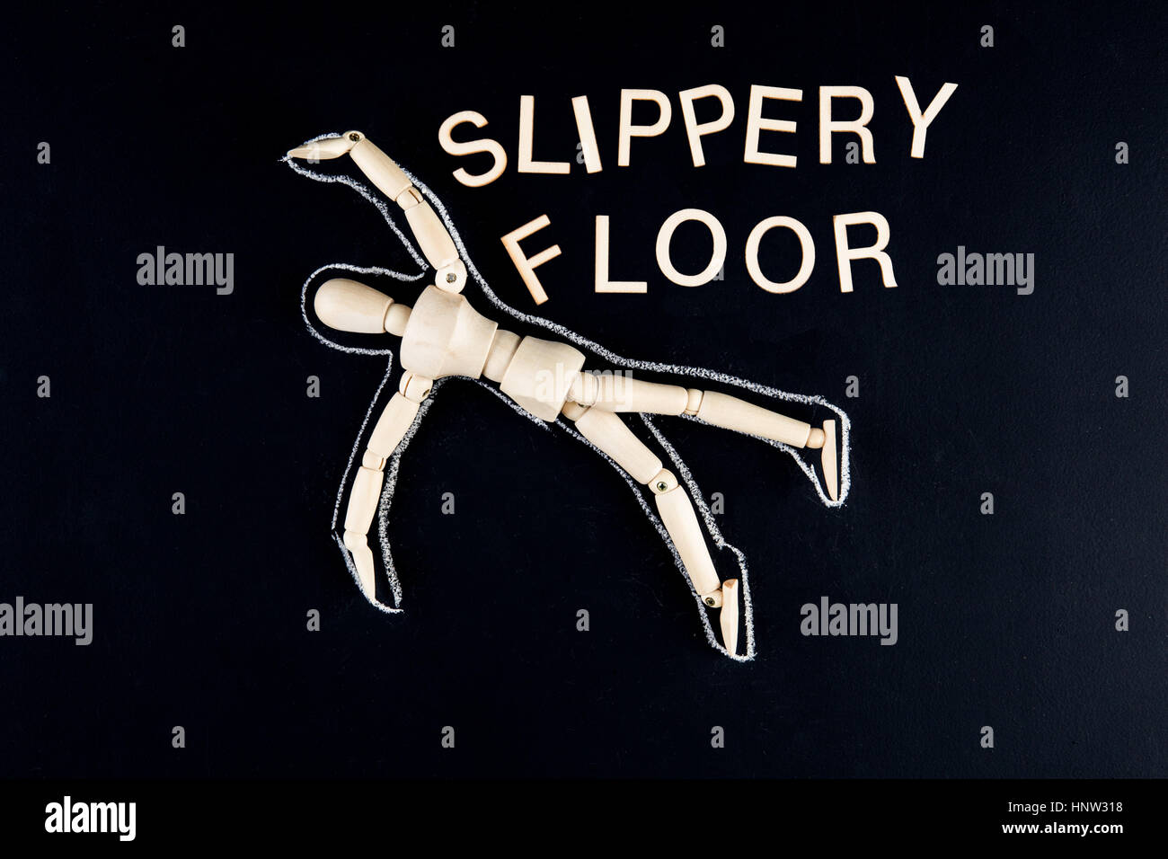 wooden dummy figurine laying on the floor with chalk outline  and 'slippery floor' text - Stock Image