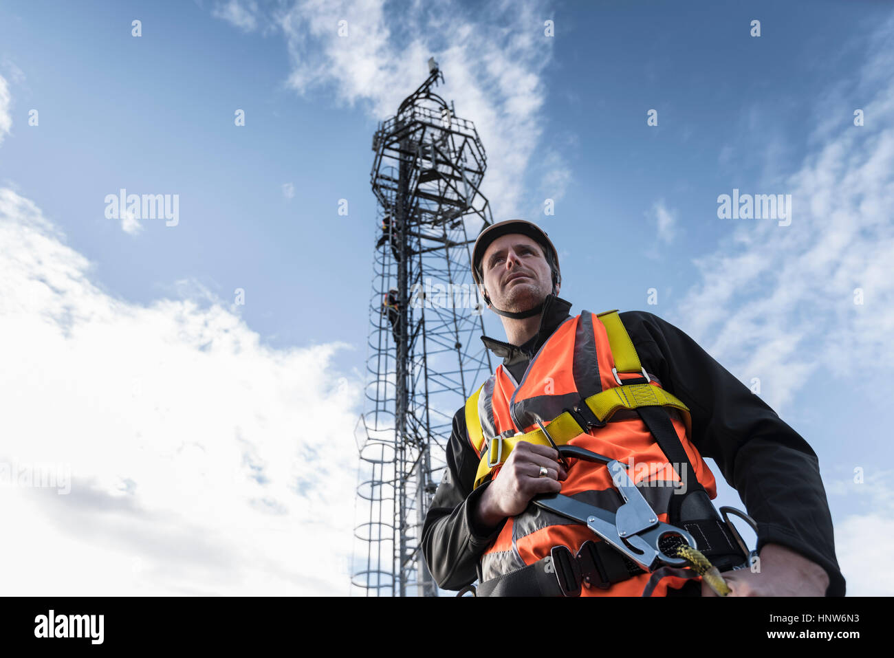 Transmission tower engineer with tower, low angle view - Stock Image