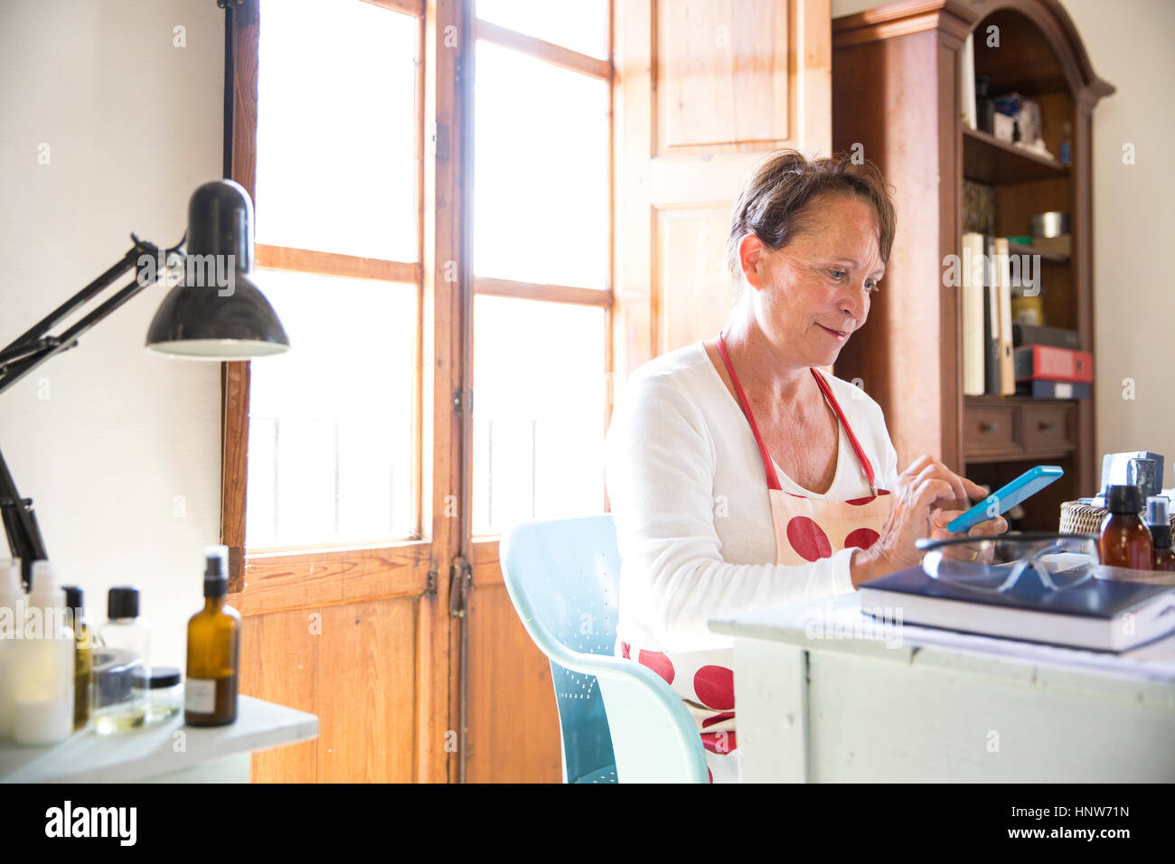 Mature woman texting on office smartphone in handmade soap workshop - Stock Image