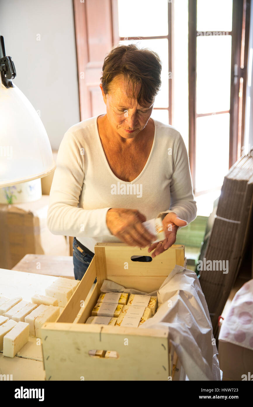 Woman packing soap bars in handmade soap workshop - Stock Image