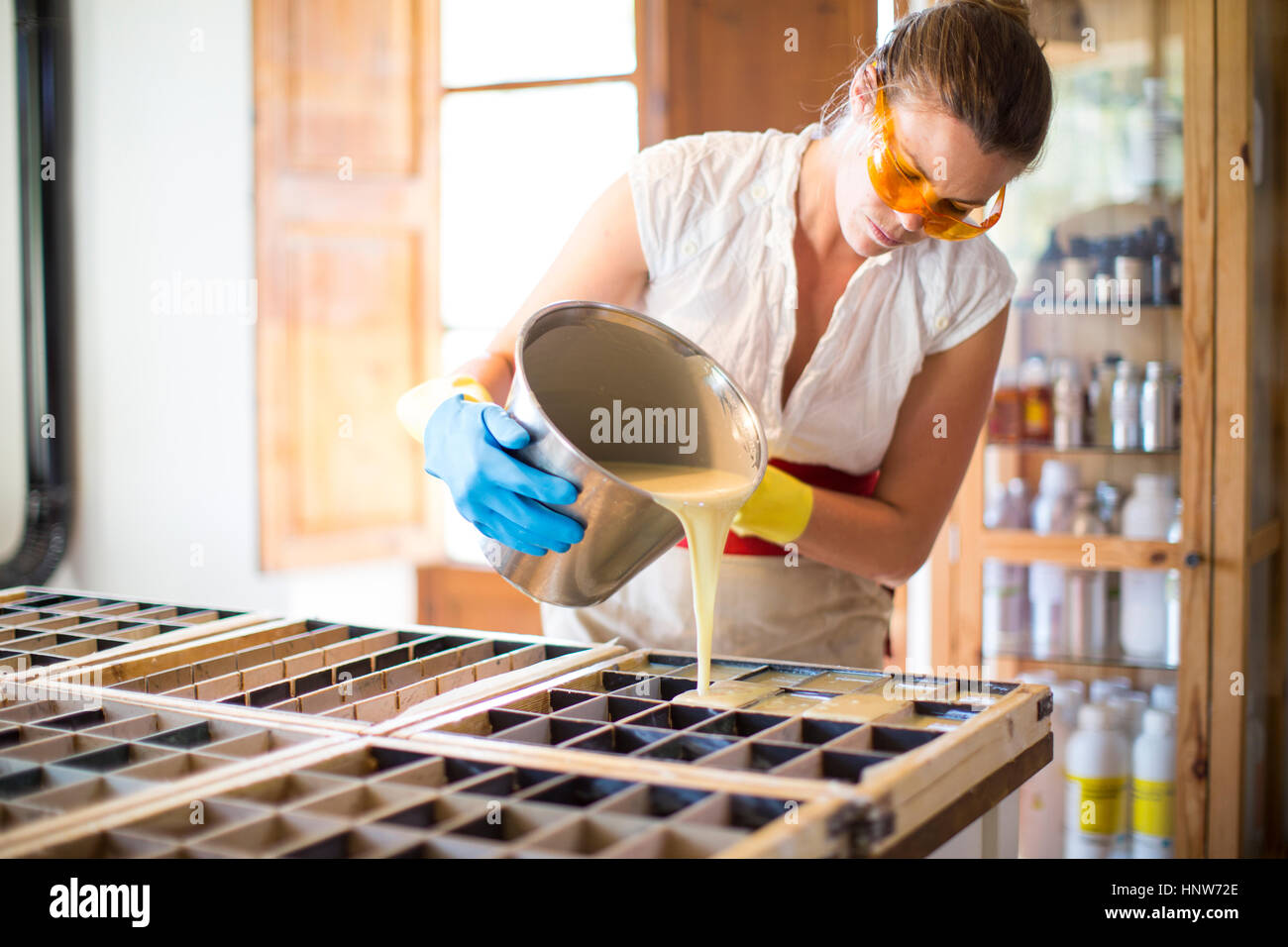 Young woman pouring liquid into soap mould in handmade soap workshop - Stock Image