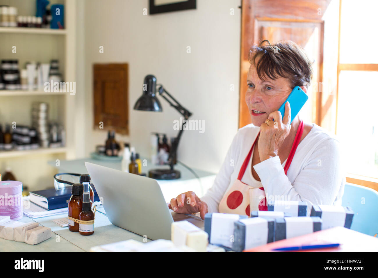 Woman talking on smartphone in handmade soap workshop office Stock Photo