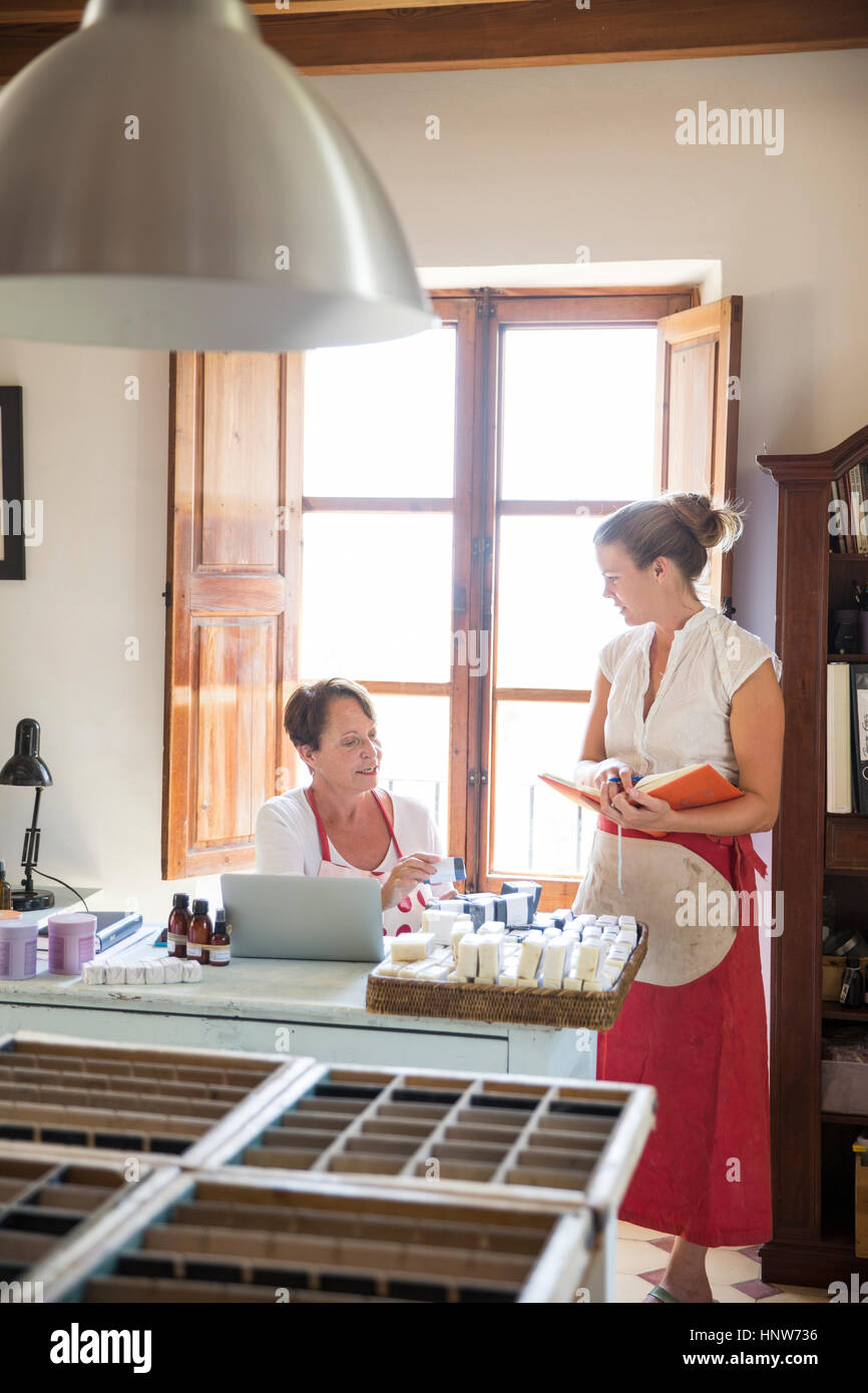 Female business owner checking quality of soap bars in handmade soap workshop office - Stock Image
