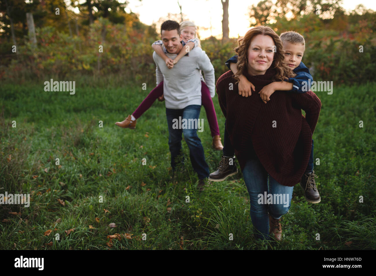 Parents giving children piggy back in field - Stock Image