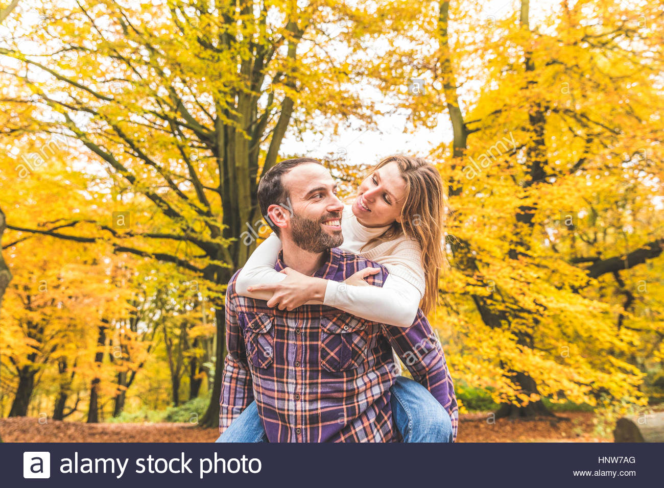 Mid adult couple in park, man giving woman piggyback - Stock Image