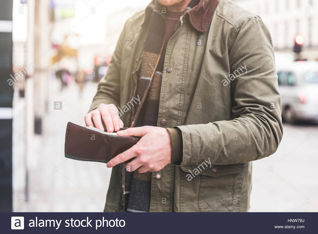 Man checking wallet in front of shop, London, UK - Stock Image