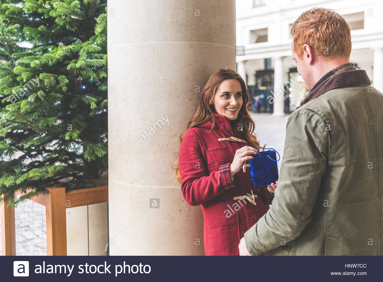 Man and woman chatting against column, Covent Garden, London, UK - Stock Image
