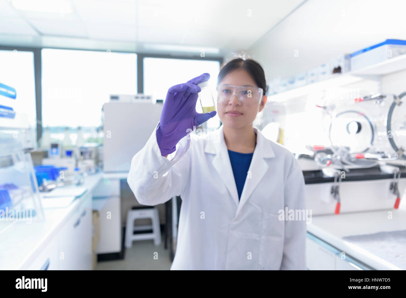 Scientist inspecting modified crystal shape material in crystal engineering research laboratory - Stock Image