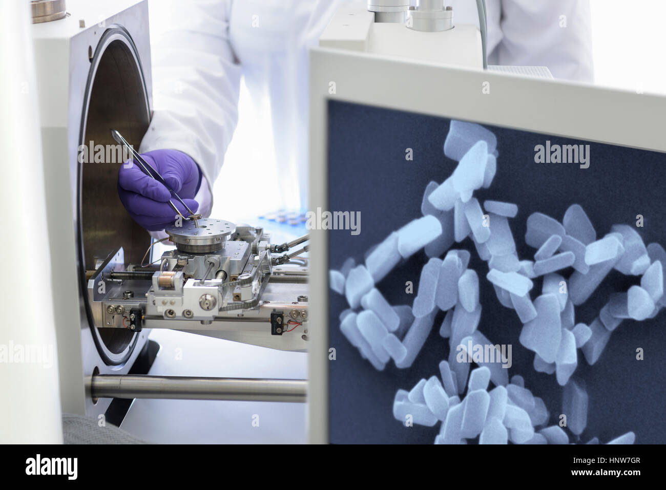 Scientist placing sample in electron microscope with image of crystals in crystal engineering research laboratory - Stock Image