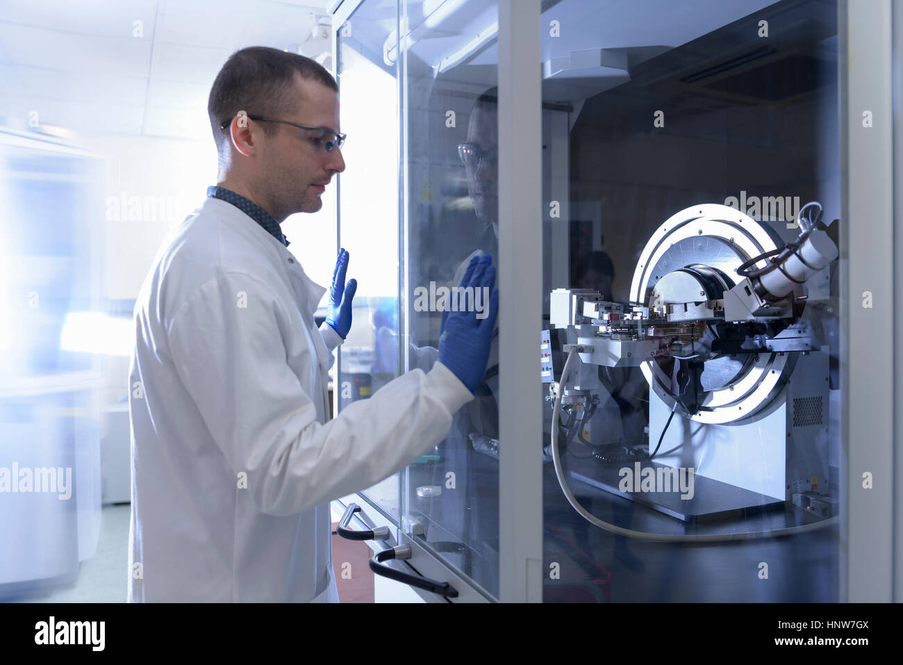 Scientist operating crystal x-ray diffraction machine in crystal engineering research laboratory - Stock Image