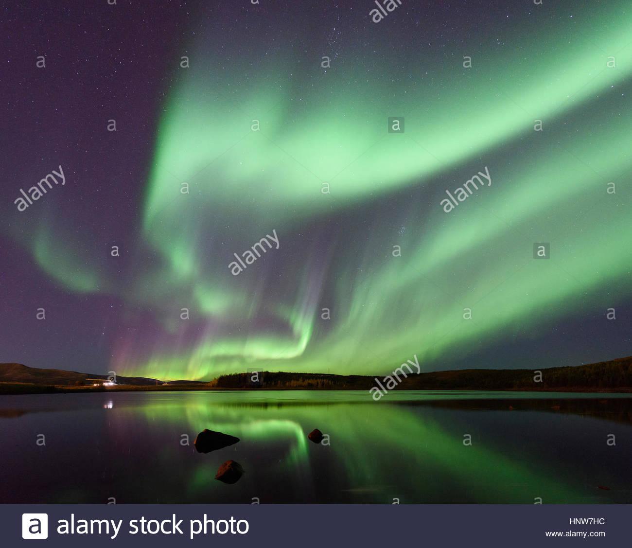 Aurora borealis over water at night, Thingvellir, Iceland - Stock Image