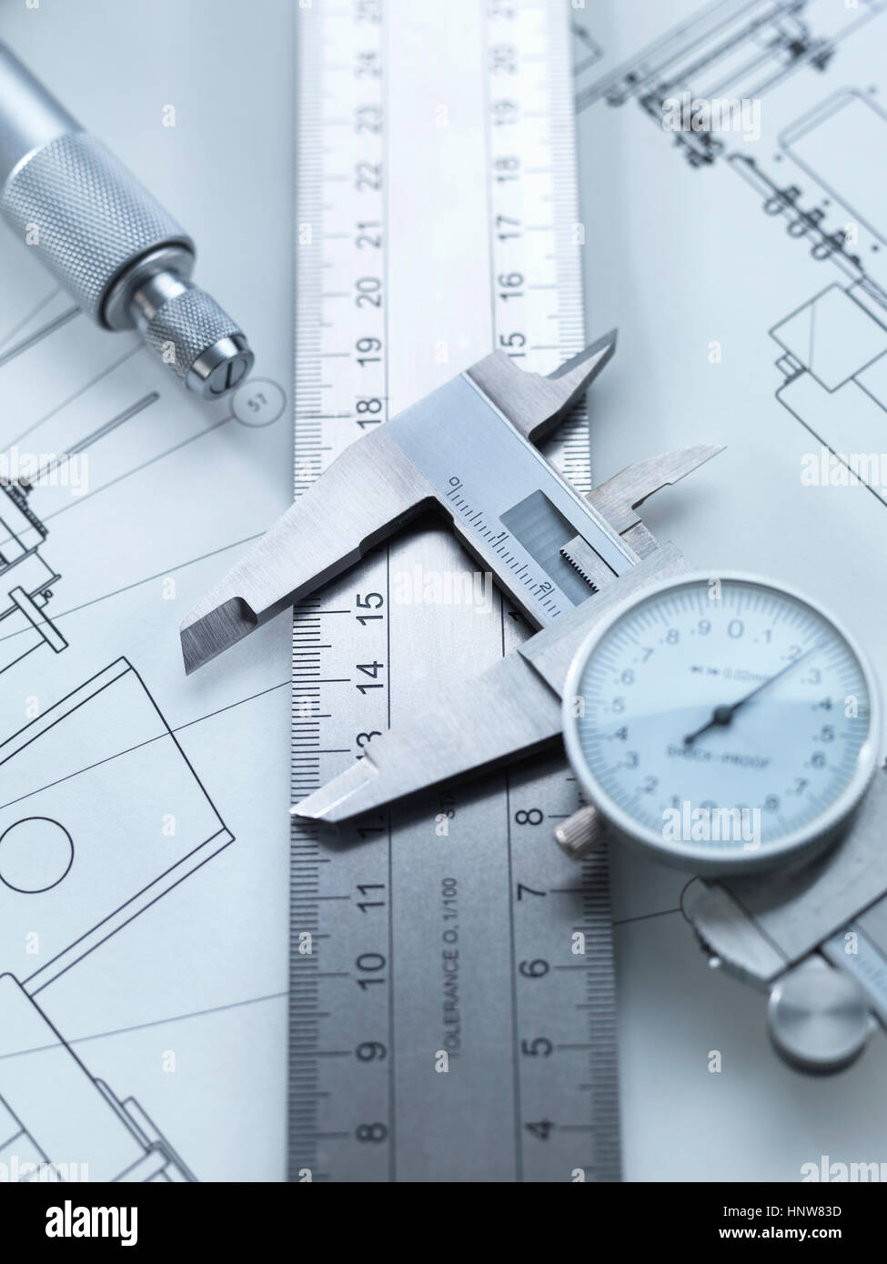 Dial calipers sitting on steel rule with engineering drawings - Stock Image