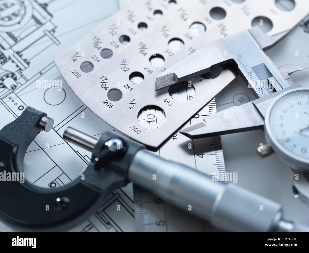 Engineering Measurement, Dial calipers sitting on a steel rule with micrometer and engineering drawings - Stock Image