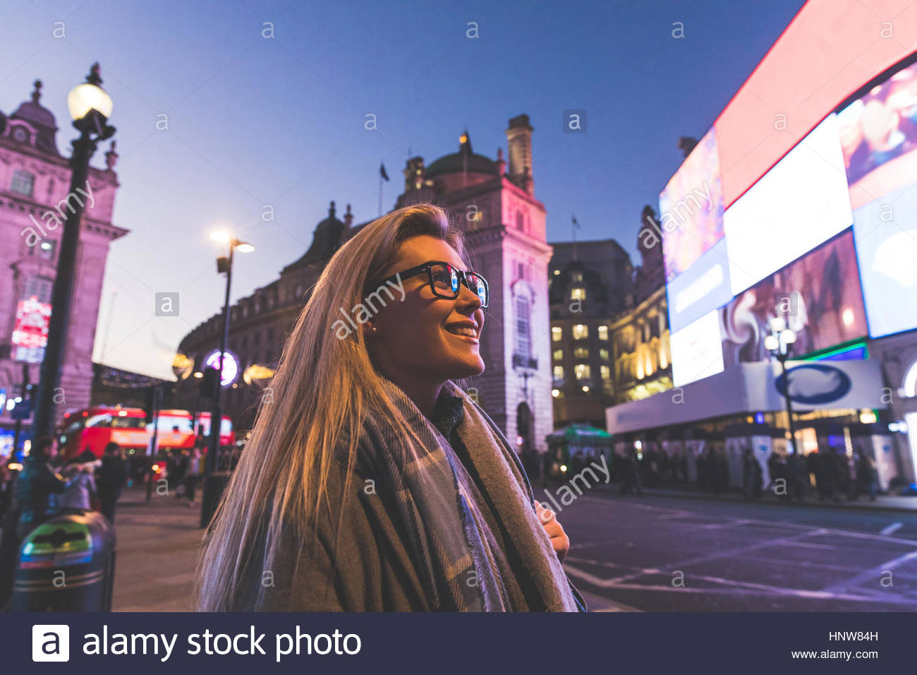 Young woman exploring city at dusk - Stock Image