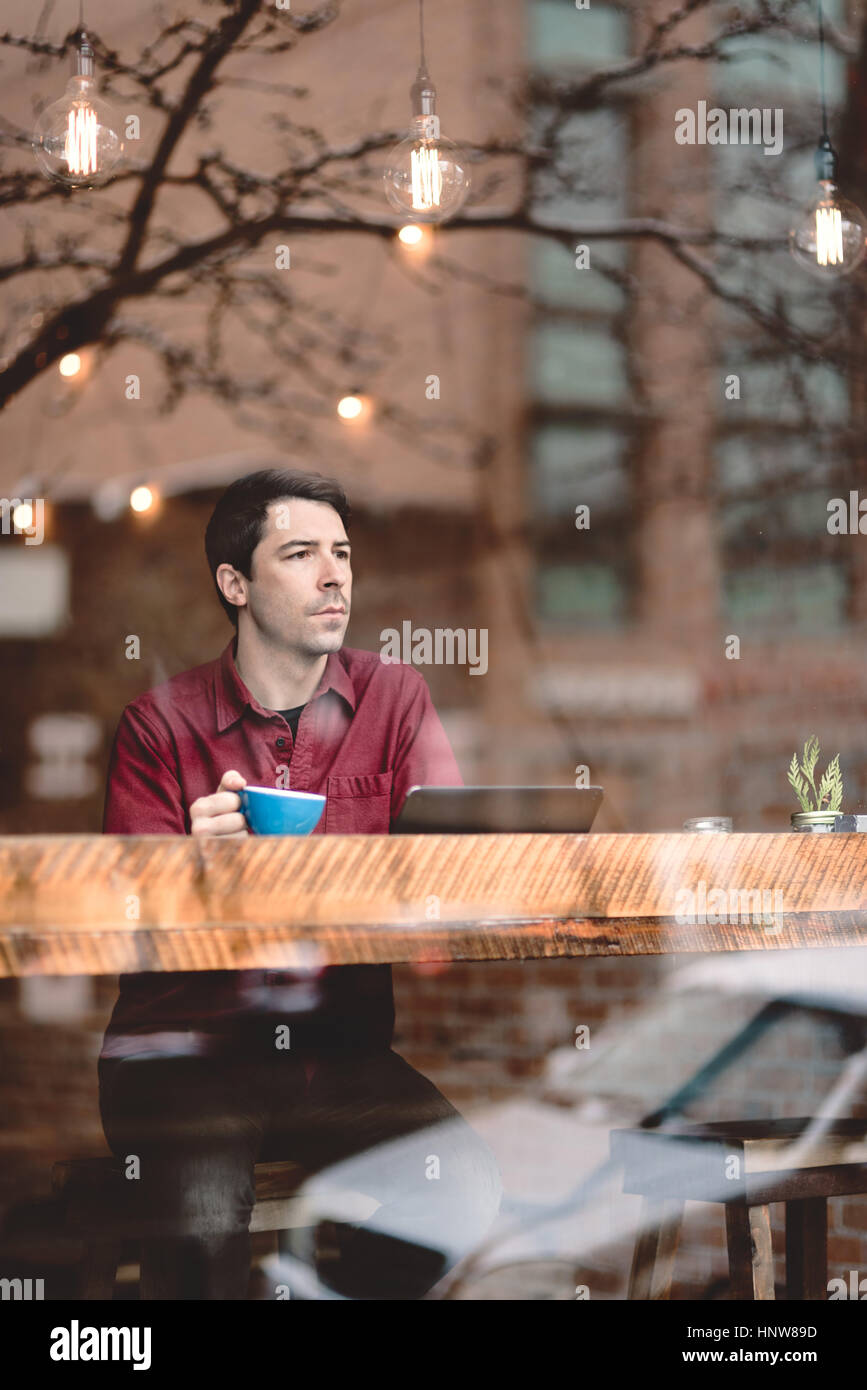 Man looking through window of cafe - Stock Image