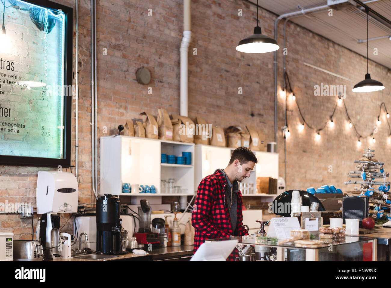 Barista preparing coffee in cafe - Stock Image