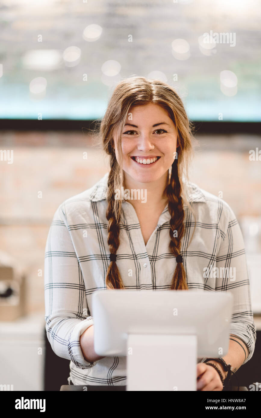 Cashier behind cash register in cafe - Stock Image