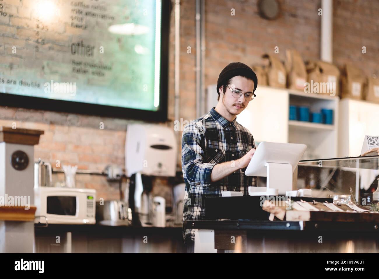 Cashier Using Cash Register In Cafe