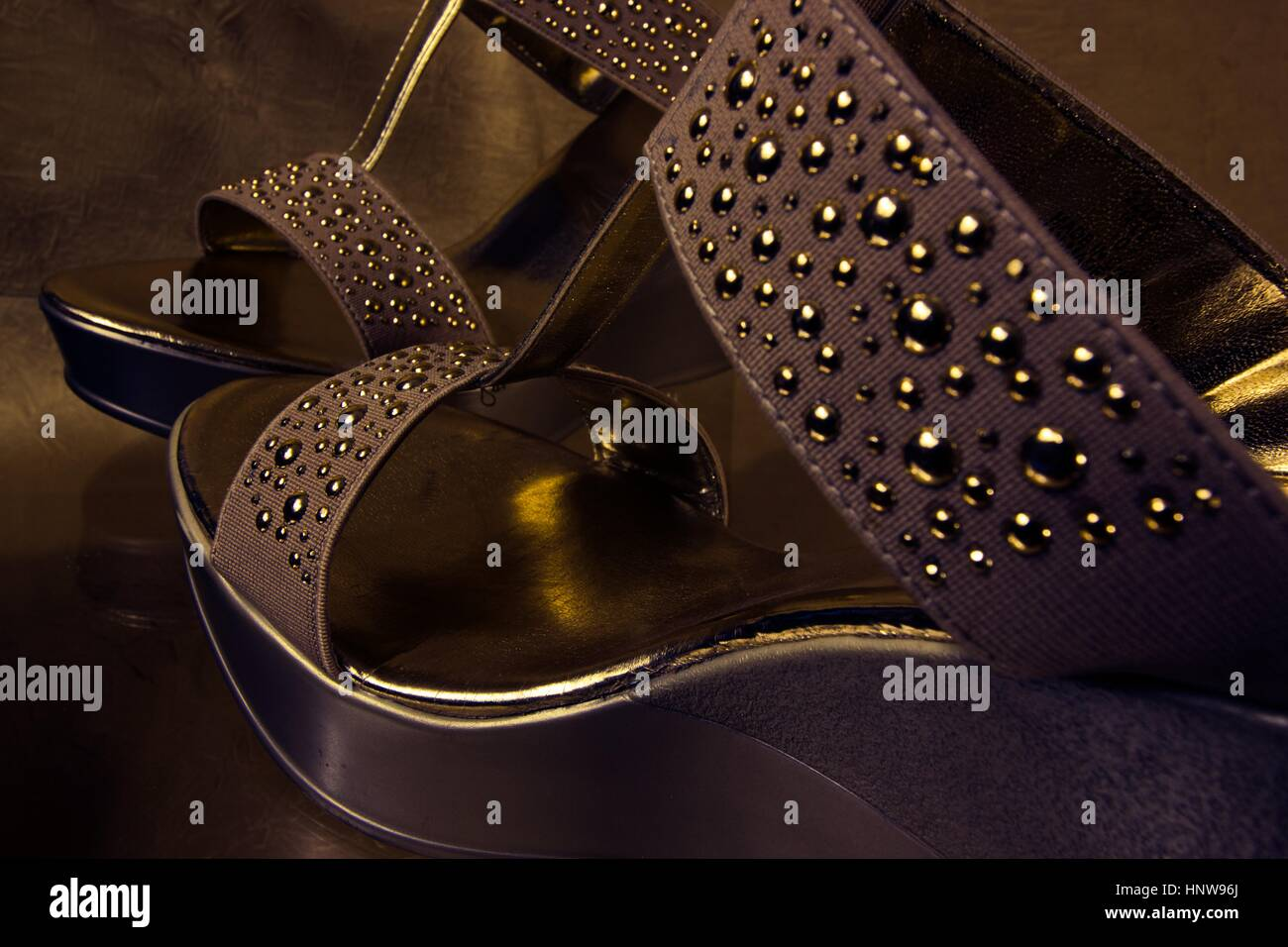 Sassy golden shoes in twilight - Stock Image