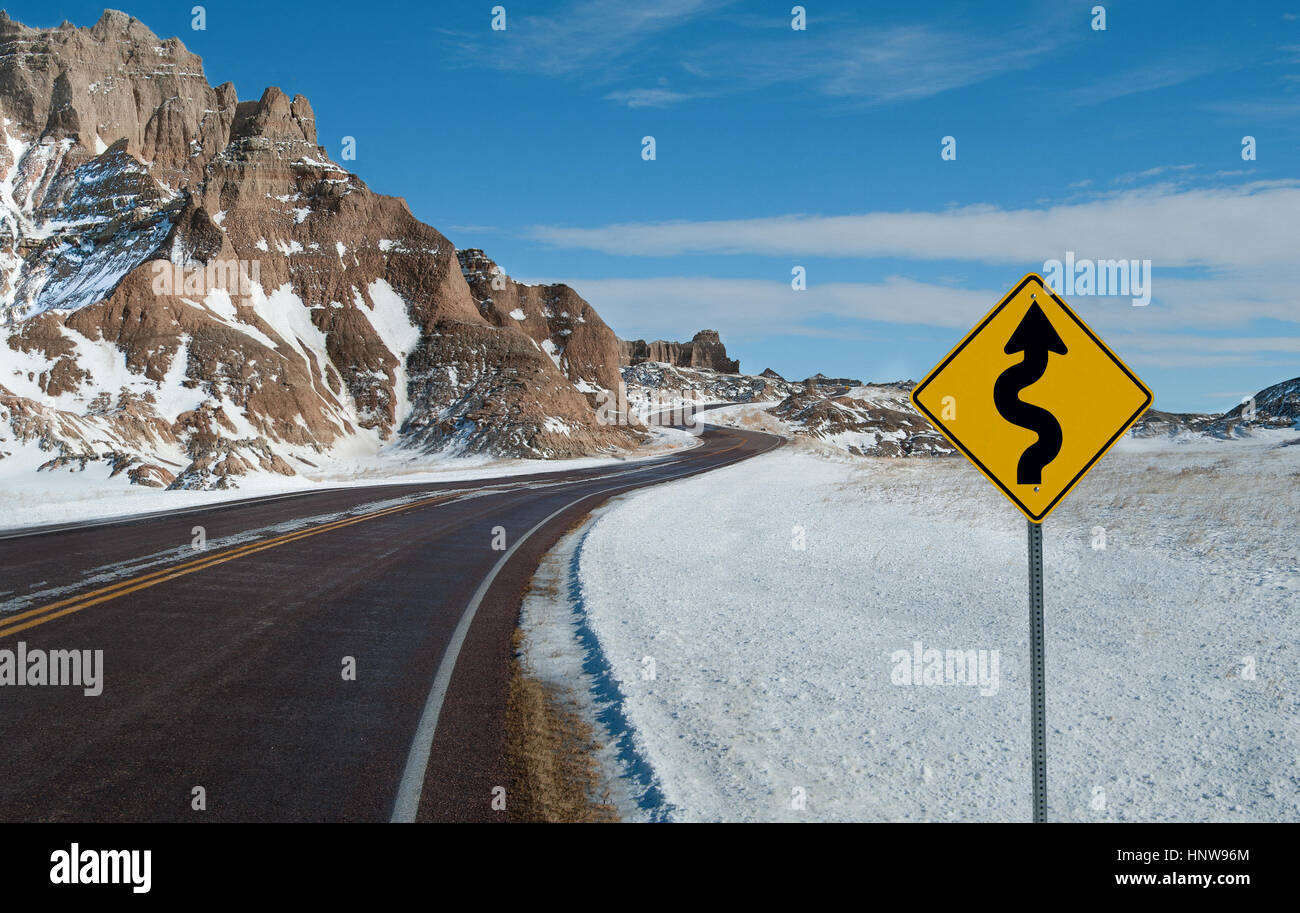 Sharp Curves Warning Sign:  A sign warns of a twisting road ahead on a winter day in Badlands National Park. - Stock Image