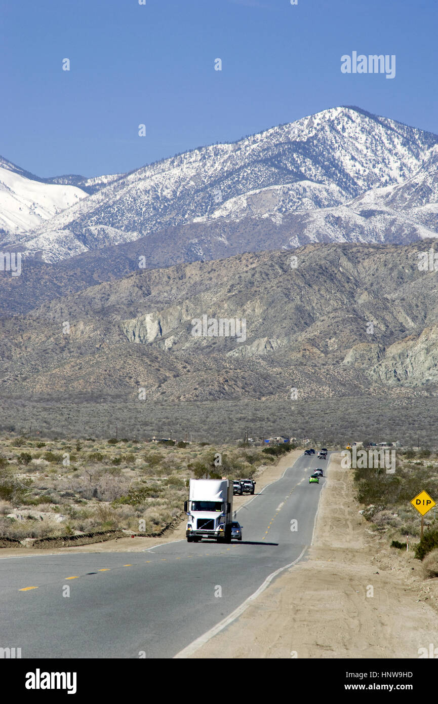 Truck on road in the Palm Desert with mountains with snow near Palm Springs, CA - Stock Image