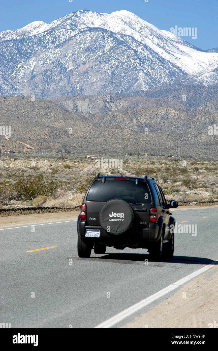 Jeep on road in the Palm Desert with mountains with snow near Palm Springs - Stock Image