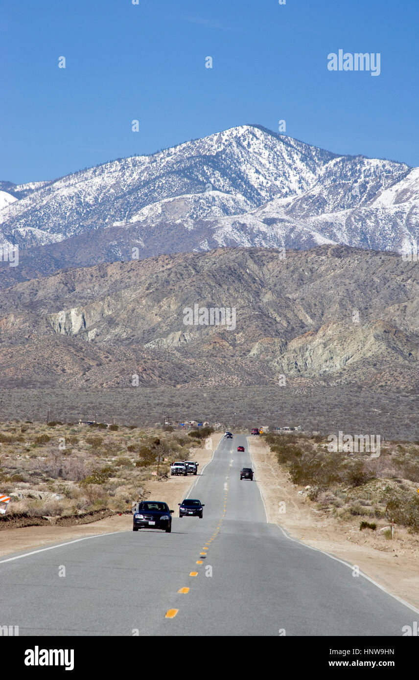 Cars on road in the Palm Desert with mountains with snow near Palm Springs - Stock Image