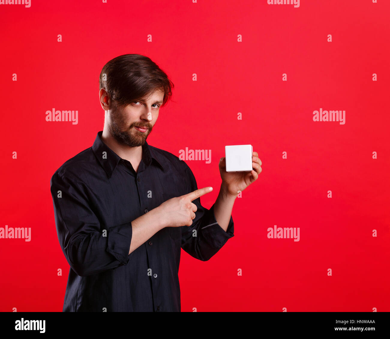 Man holding an empty cube. Advertising Space. Attractive man shows space for copy. Forefinger. He explains something - Stock Image