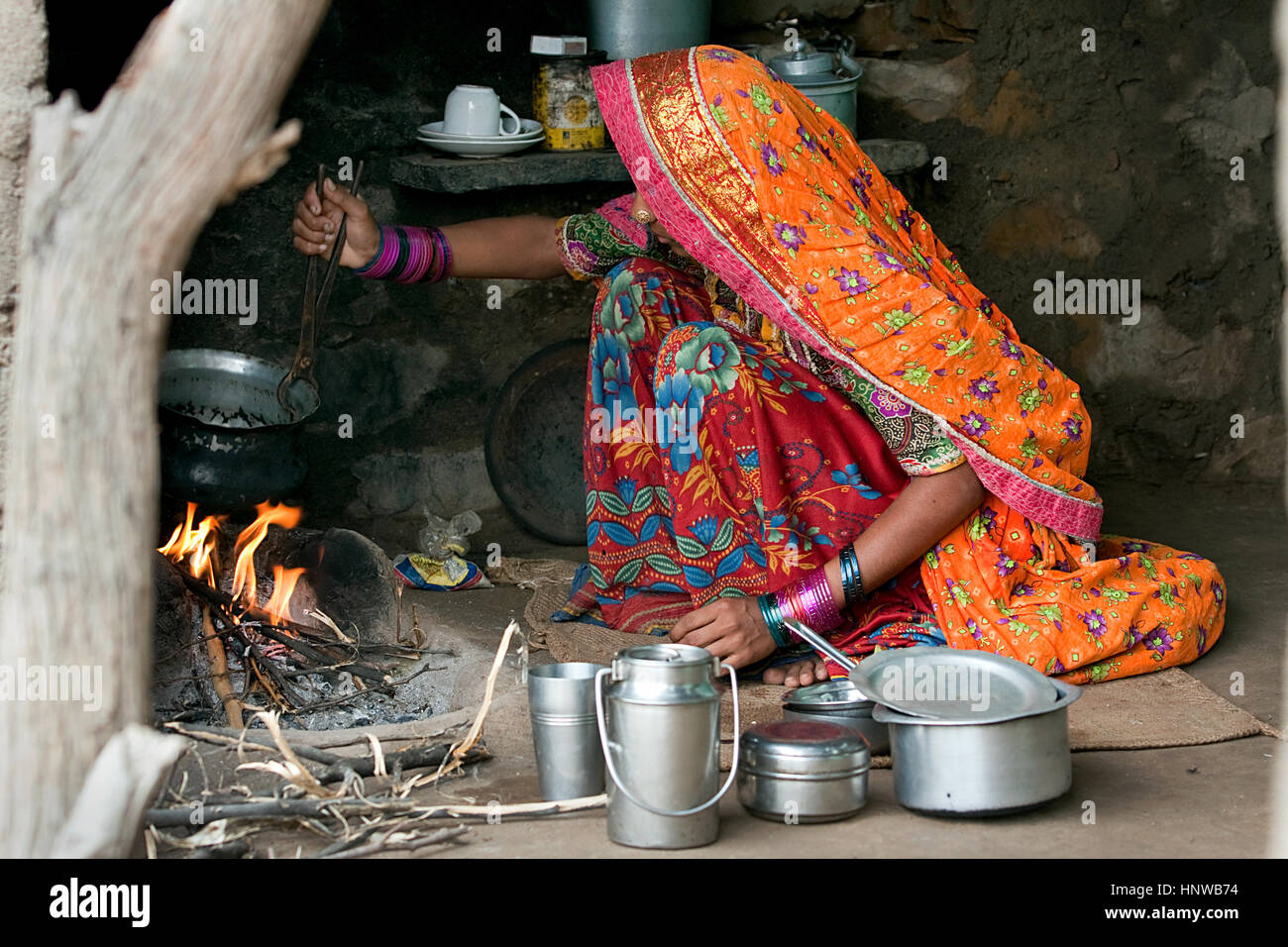 A Kutch - Kachchh, Gujarat, india village woman making food on bonfire wearing colourful clothes in her typical - Stock Image