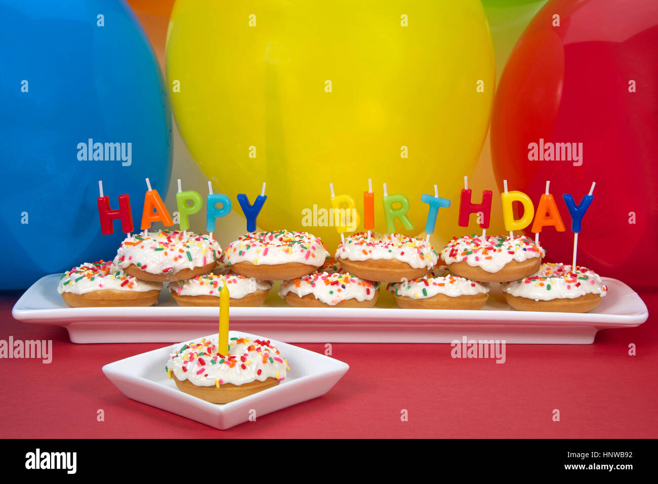Miniature Donut Cake On Long White Plate With Happy Birthday Candles One Single Square Yellow Candle Perfect 1st