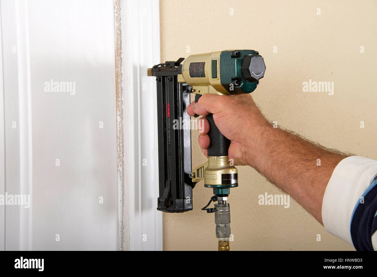 Do it yourself home owner repairing door frame molding with nail gun ...