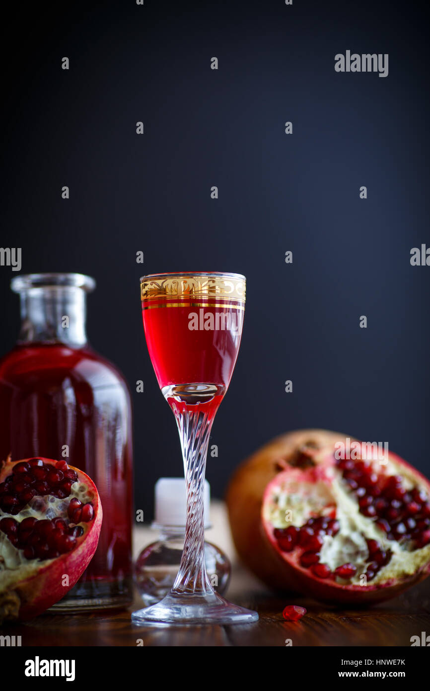 sweet pomegranate fruit alcoholic cordial in the decanter with a glass on a dark table - Stock Image