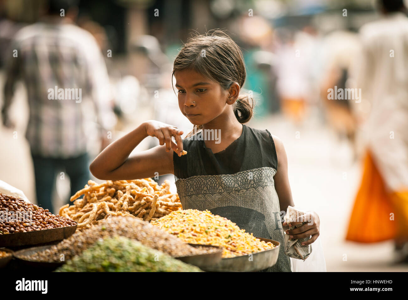 Rishikesh, India - September 23,2014: Indian girl buying sweets from the street stall in Rishikesh, India on September - Stock Image