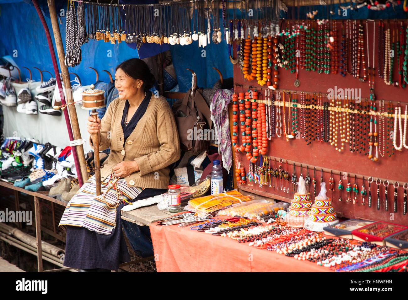 Dharamsala, India - 28 September, 2014: Tibetian woman praying with traditional hand prayer wheel at the street - Stock Image