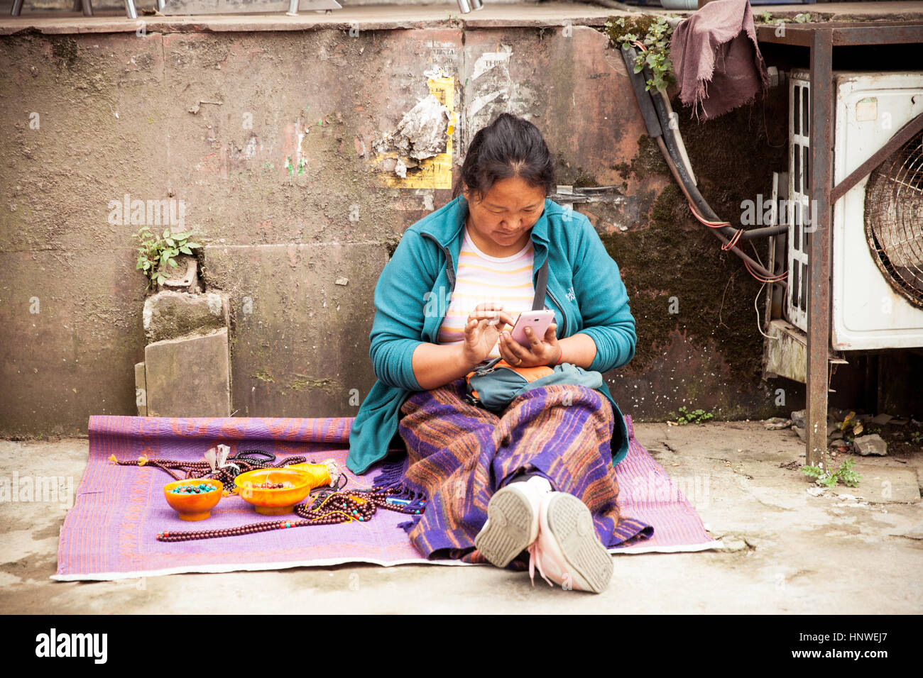 Dharamsala, India - 28 September, 2014: Tibetian woman with a smartphone at the street market, Dharamsala, India. - Stock Image