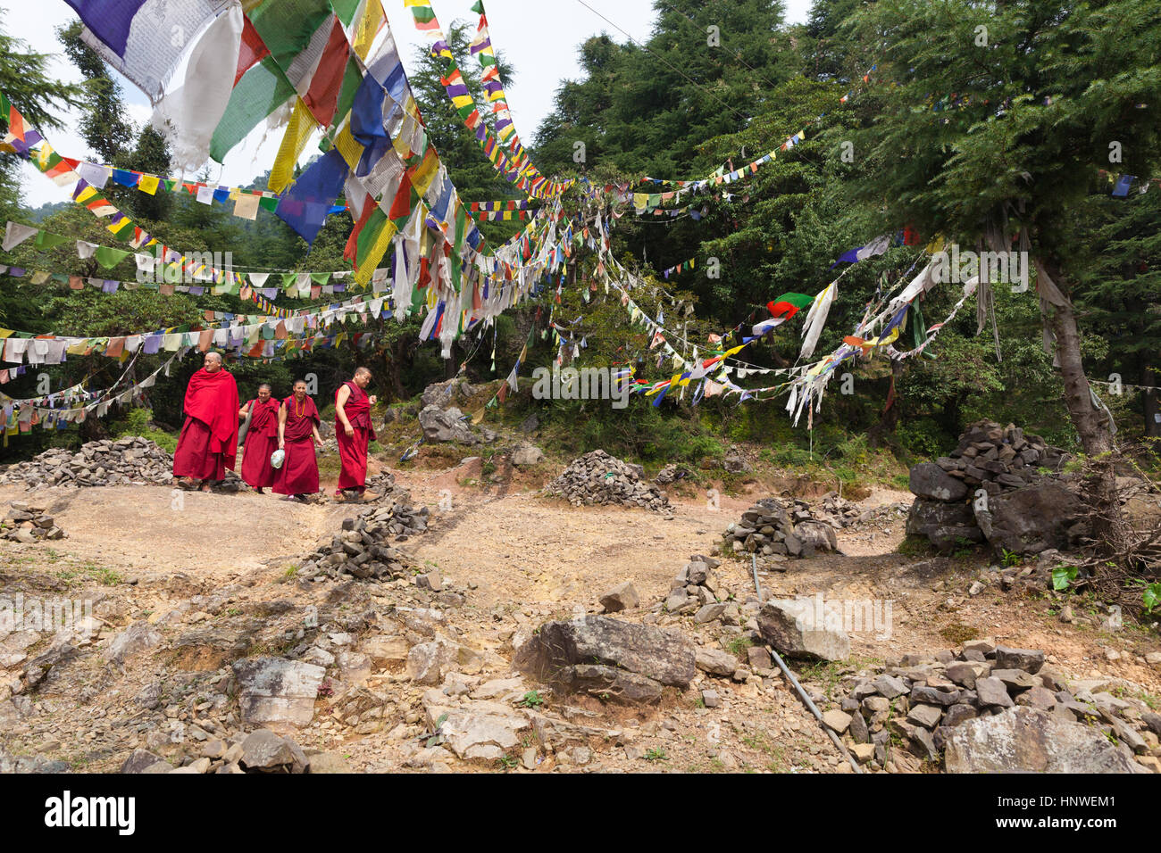 Dharamsala, India - 27 September 2014: Buddhist monks walking under prayer flags in the mountains near McLeod Ganj - Stock Image