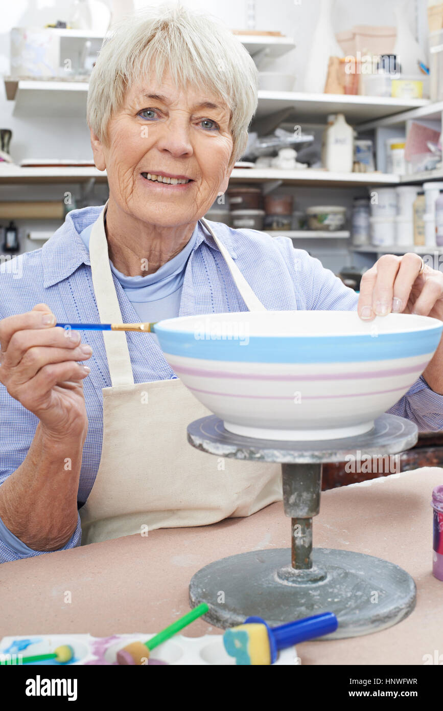 Senior Woman Decorating Bowl In Pottery Class - Stock Image