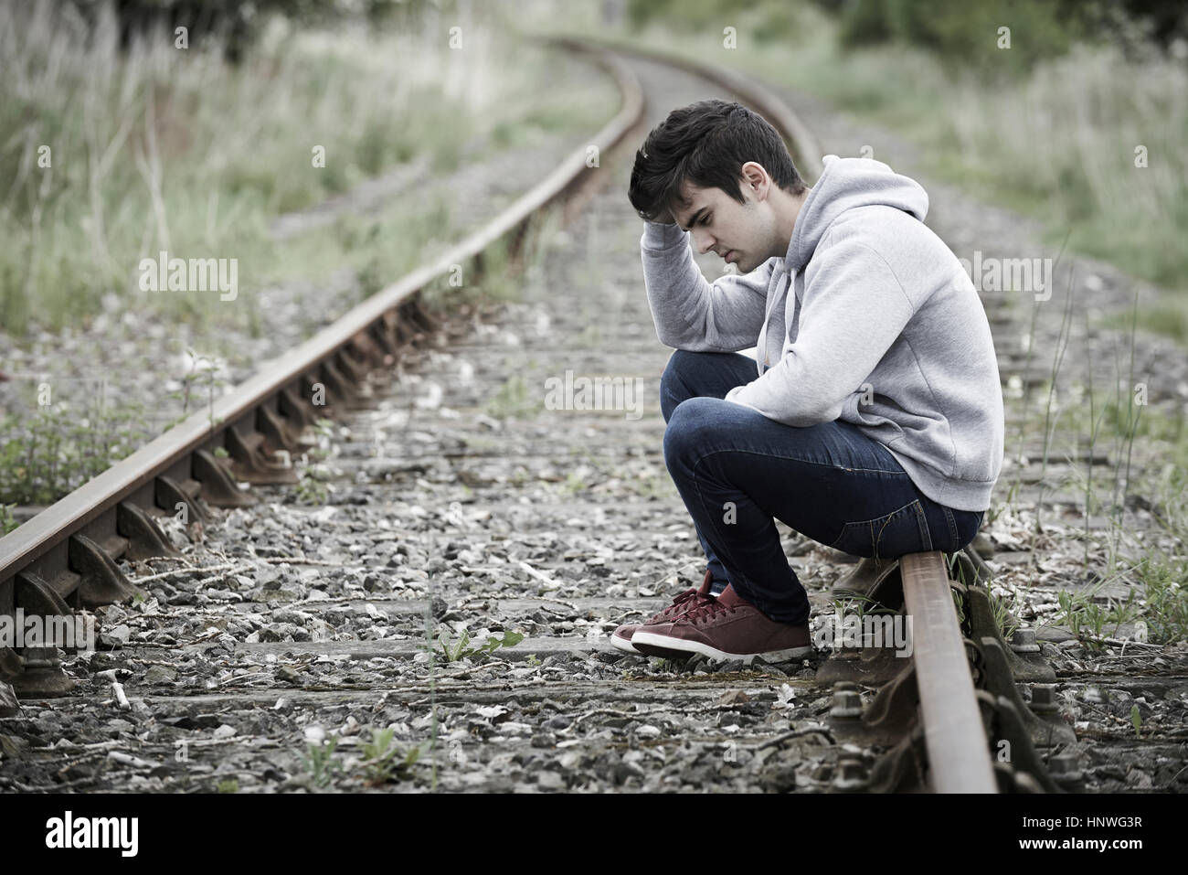 Depressed Young Man Sitting On Railway Track - Stock Image