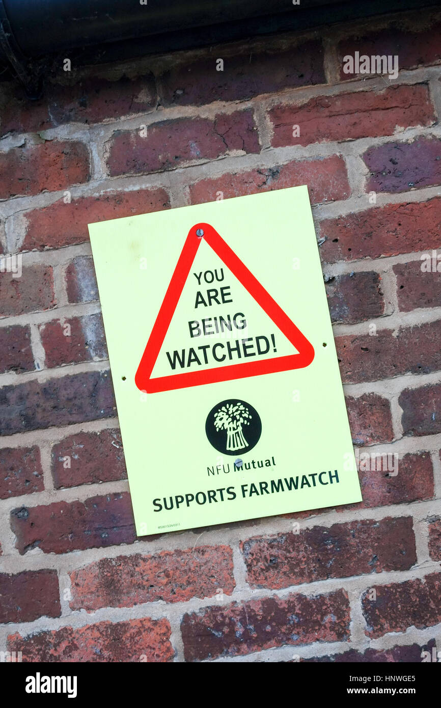 A sign on farm building saying 'You are being watched', supplied by, National Farmers Union, mutual, supports, - Stock Image