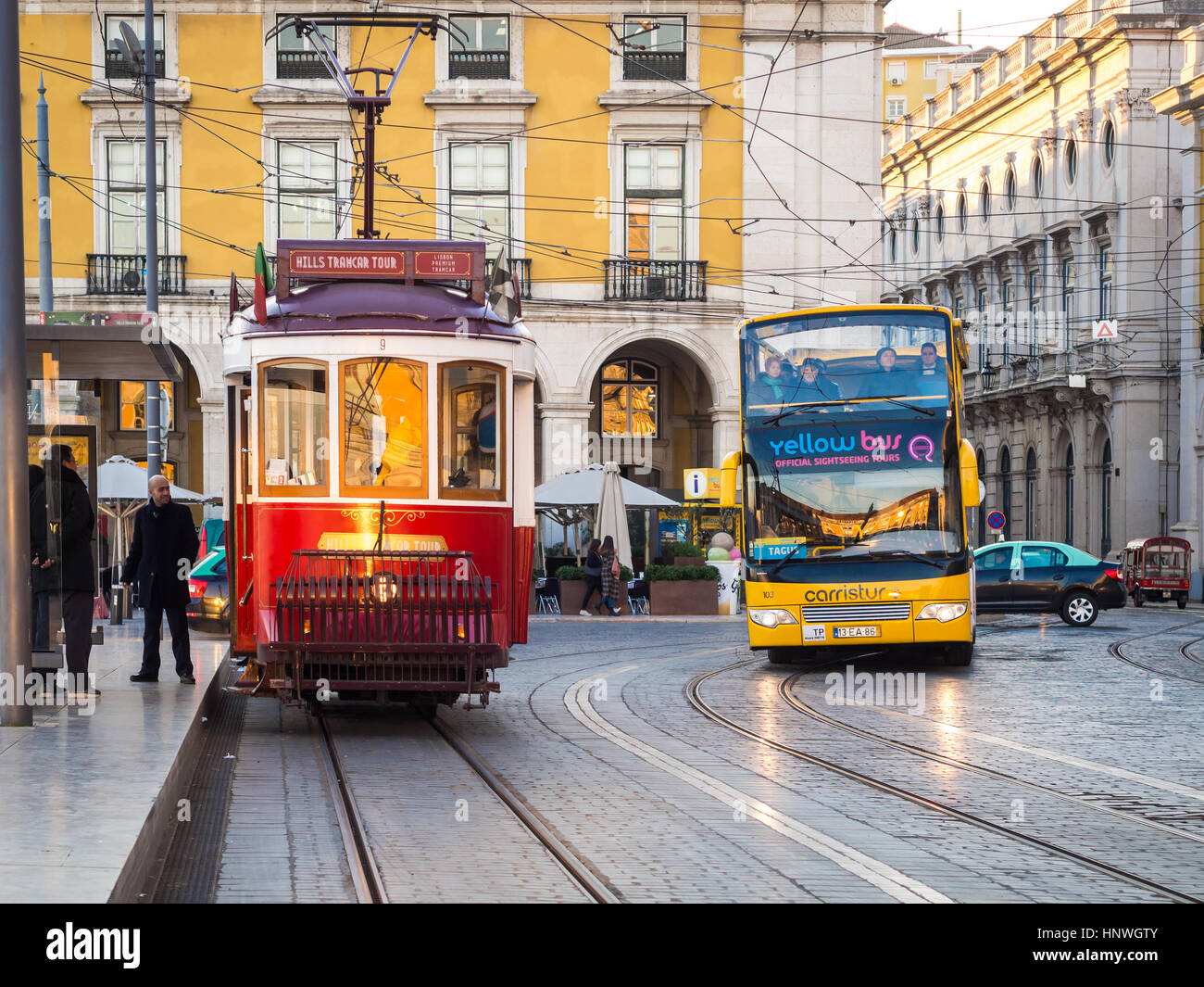 LISBON, PORTUGAL - JANUARY 10, 2017: Transport in Lisbon: typical old tram and a touristic bus on the Praca do Comercio - Stock Image