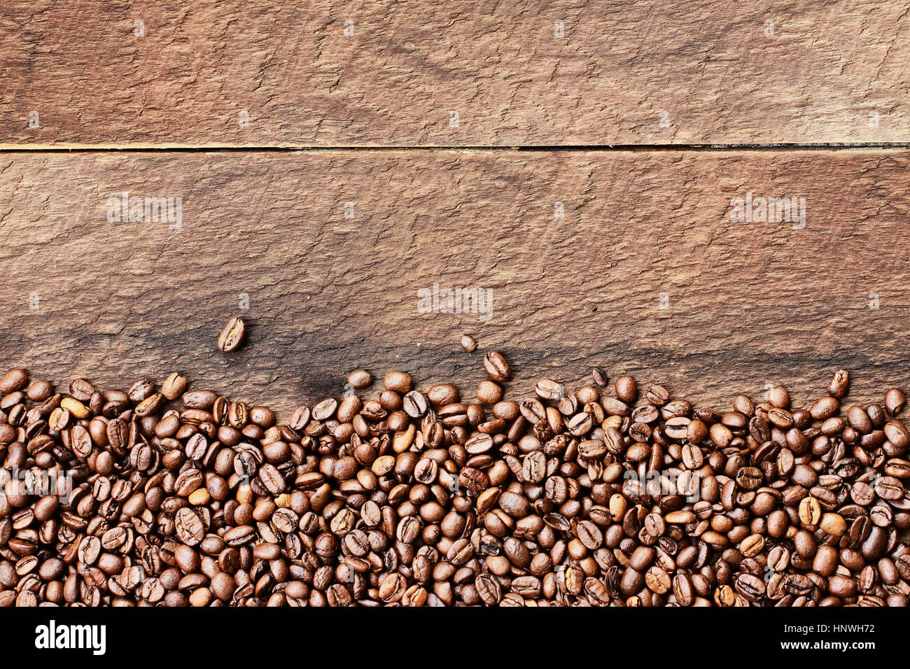 Overhead shot looking down on a flatlay image of coffee beans over a rustic wood table top background with copy - Stock Image