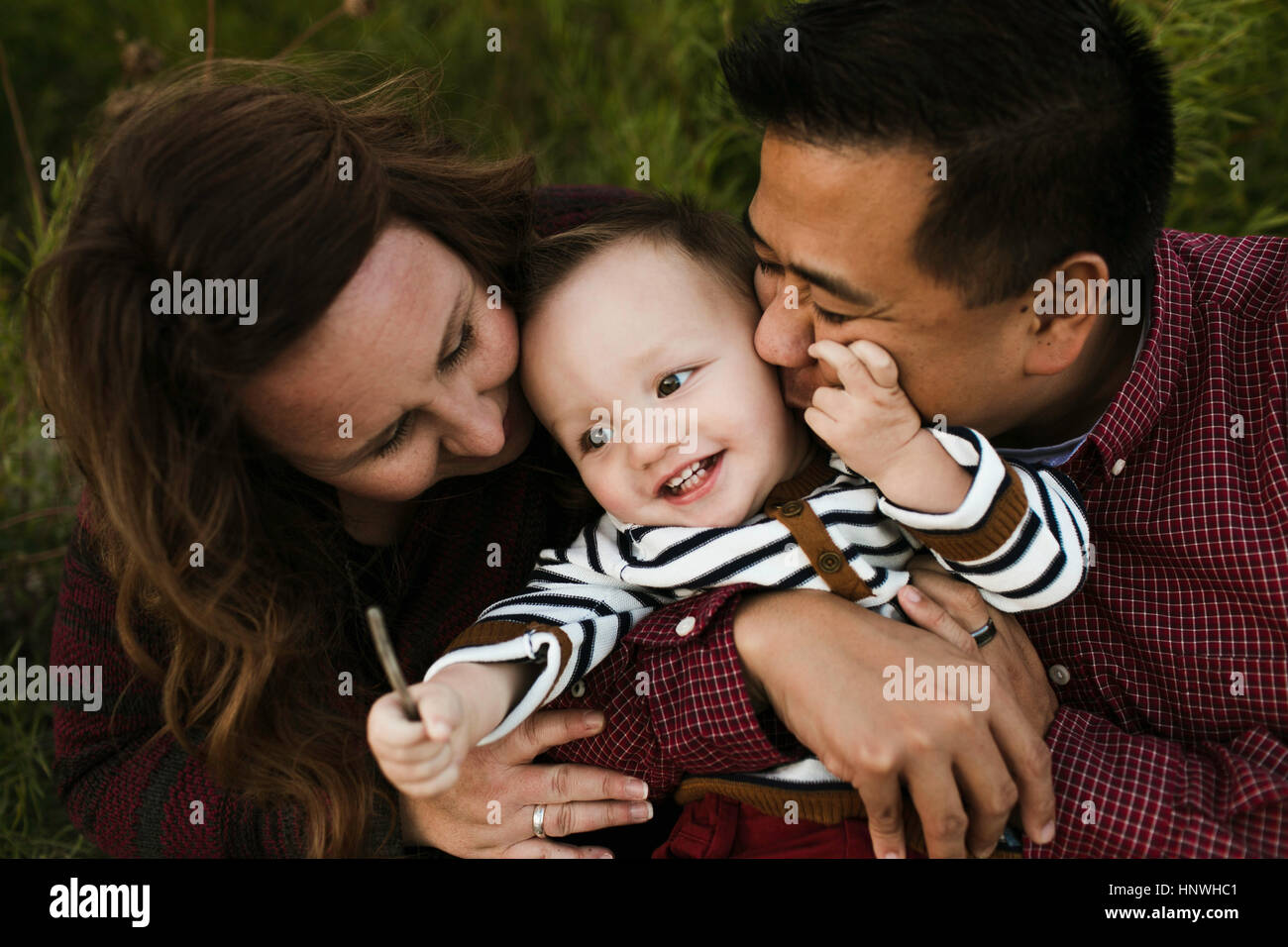 Mother and father hugging smiling baby boy - Stock Image